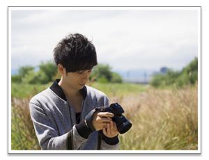 カメラを覗き込む男性